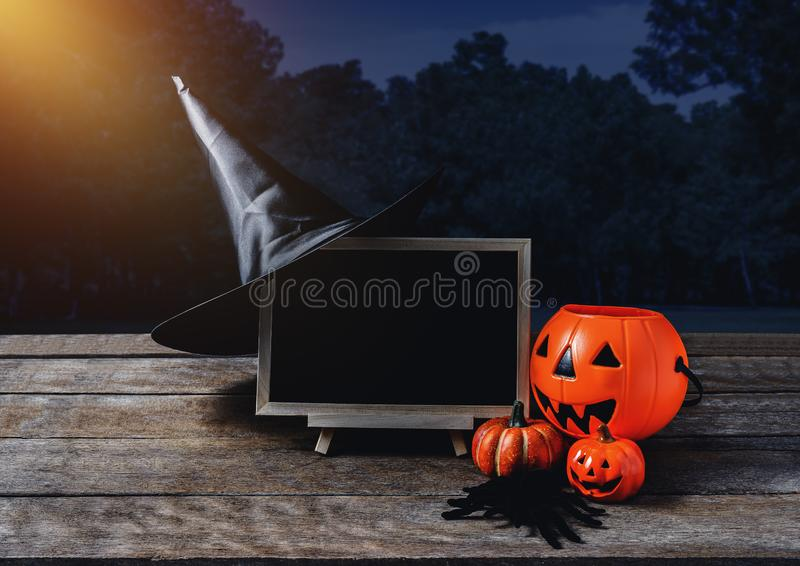 Halloween background. Spooky pumpkin, Witch hat, Black spider, c. Halkboard on wooden floor with moon and dark forest. Halloween design with copyspace stock image