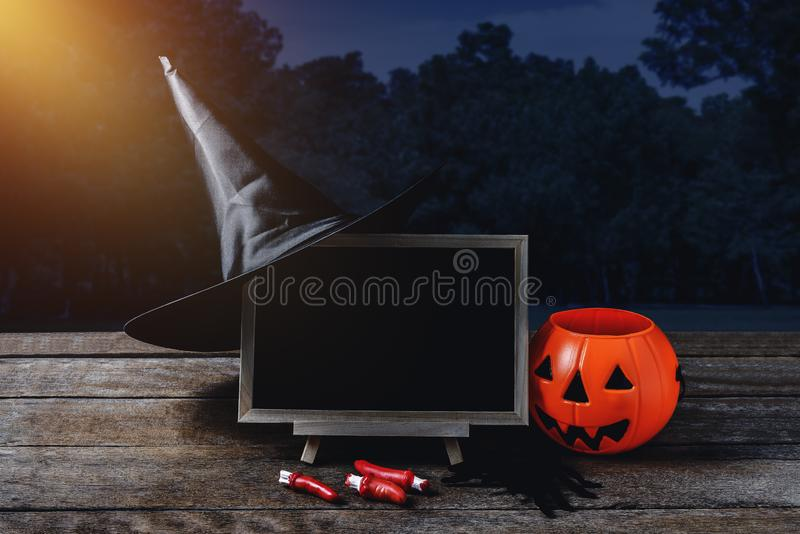 Halloween background. Spooky pumpkin, Witch hat, Black spider, c. Halkboard on wooden floor with moon and dark forest. Halloween design with copyspace royalty free stock photography