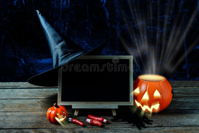 Halloween background. Spooky pumpkin, Witch hat, Black spider, c. Halkboard on wooden floor with moon and dark forest. Halloween design with copyspace royalty free stock photos