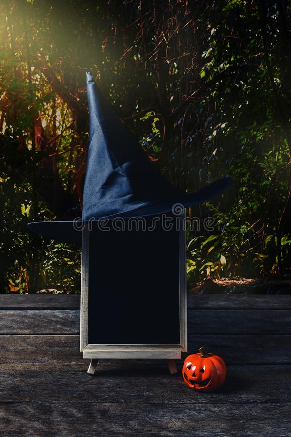 Halloween background. Spooky pumpkin, Witch hat, chalkboard on w. Ooden floor with moon and dark forest. Halloween design with copyspace stock images