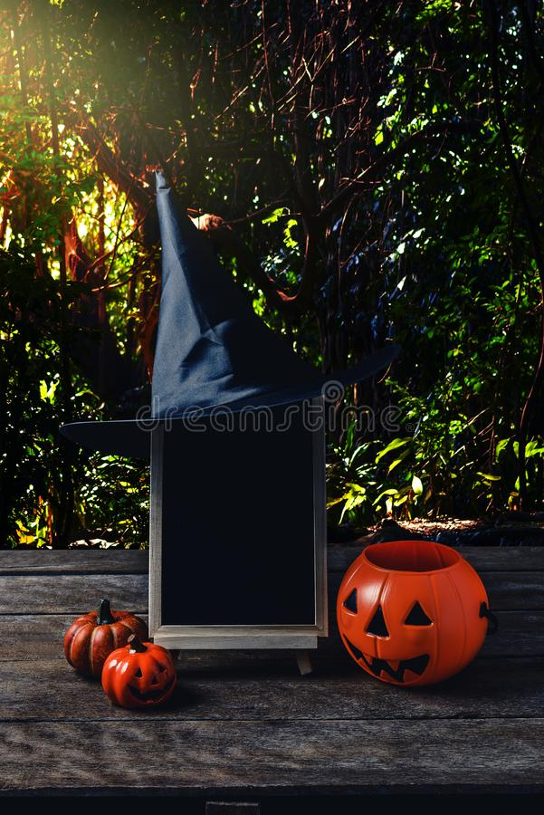 Halloween background. Spooky pumpkin, Witch hat, chalkboard on w. Ooden floor with moon and dark forest. Halloween design with copyspace stock photo