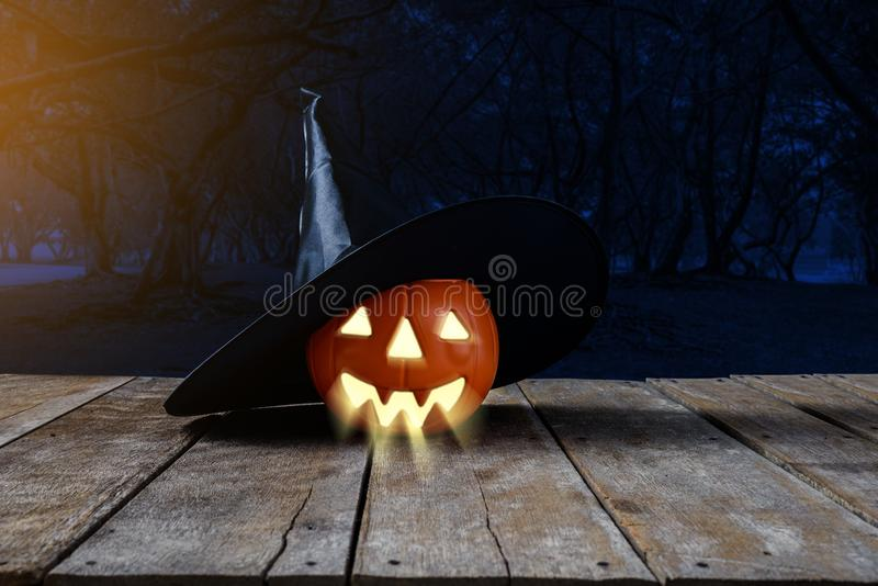 Halloween background. Spooky pumpkin, Witch hat on wooden floor royalty free stock photography