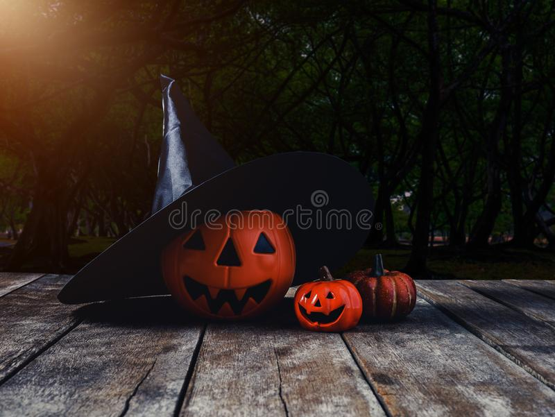Halloween background. Spooky pumpkin, Witch hat on wooden floor. With moon and dark forest. Halloween design with copyspace royalty free stock photography