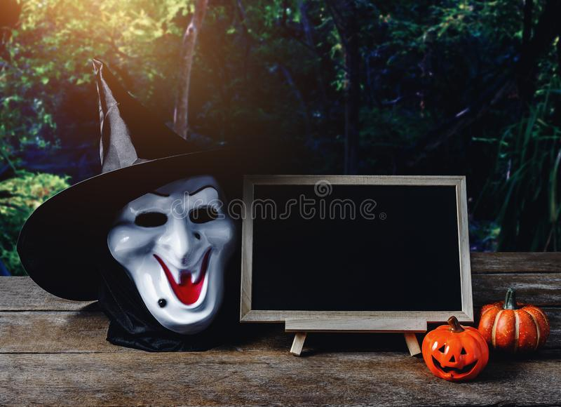 Halloween background. Spooky pumpkin, Witch mask, chalkboard on. Wooden floor with moon and dark forest. Halloween design with copyspace stock images