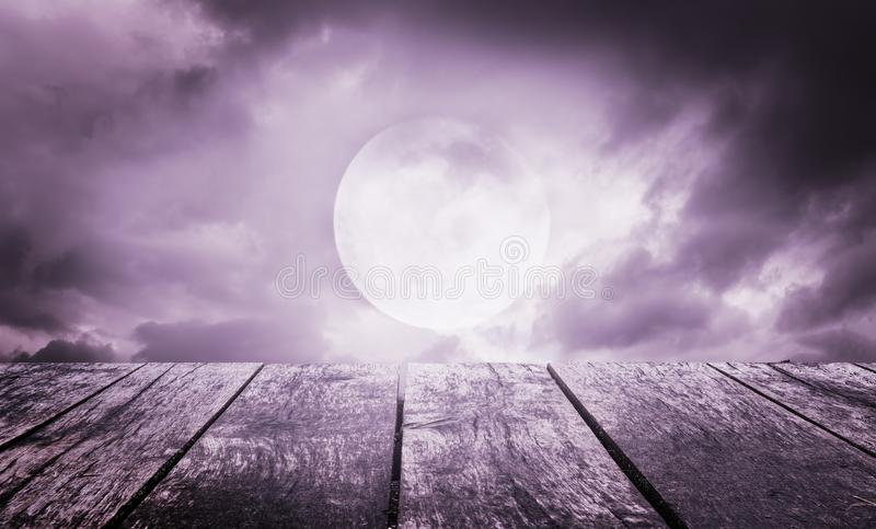 Halloween background. Spooky sky with full moon and wooden table. Halloween background. Spooky dark sky with full moon and wooden table stock photos