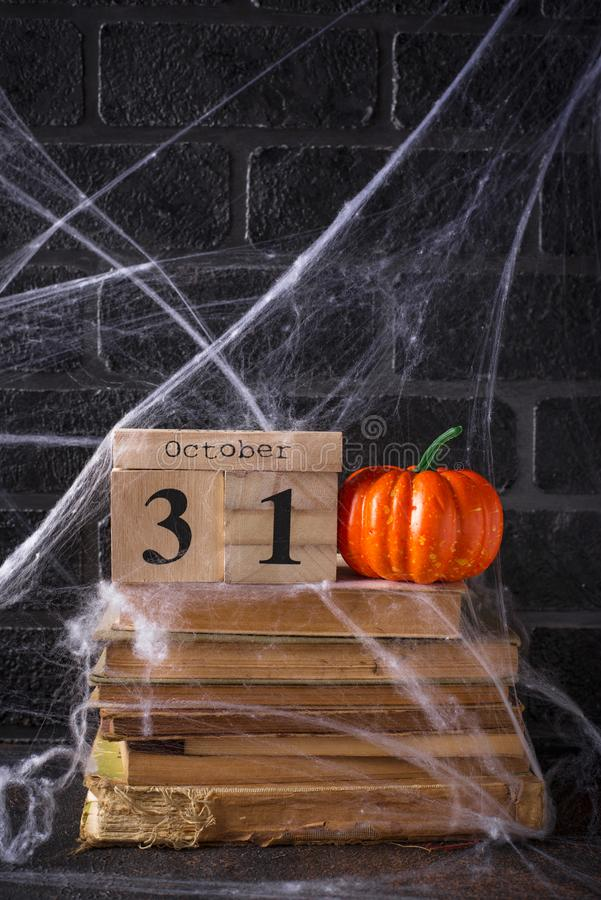 Halloween background with wooden calendar. And old books royalty free stock image