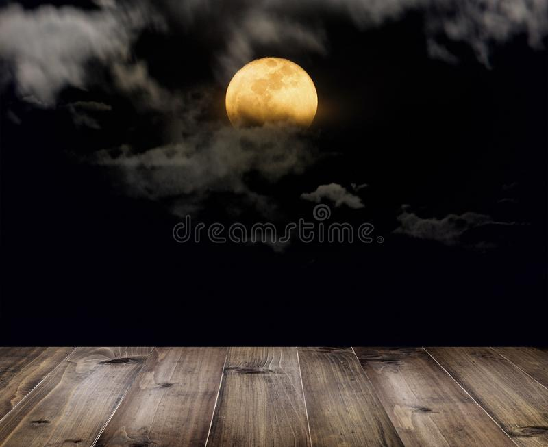 Wooden table over full moon with clouds at night. stock photos