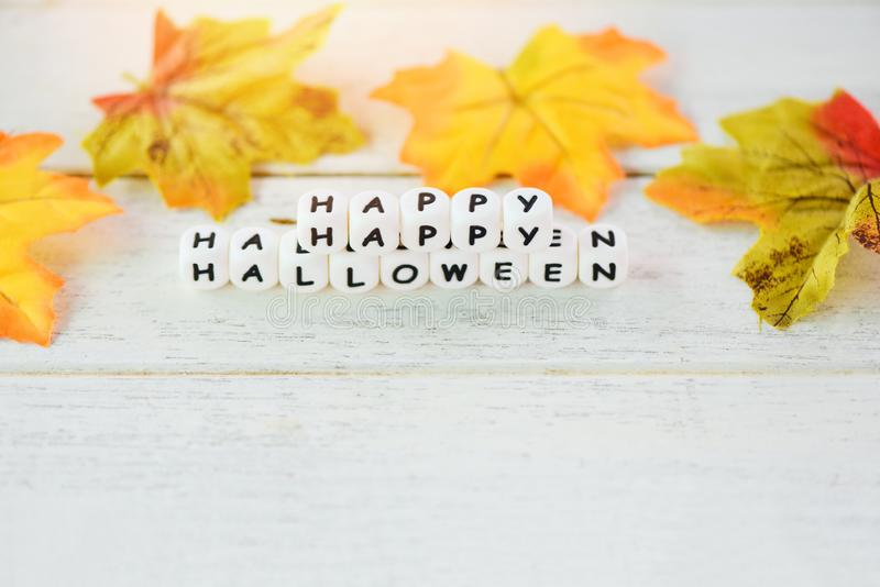 Halloween background with word blocks happy halloween decorations and leaves autumn on white wooden table holiday concept. Top view copy space stock images