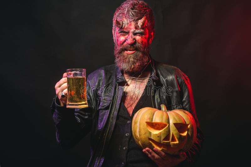 Halloween bad habits and addiction concept. Hipster demon drink beer on black background. Holiday celebration and party. Devil smile with glass mug. Man with stock photos