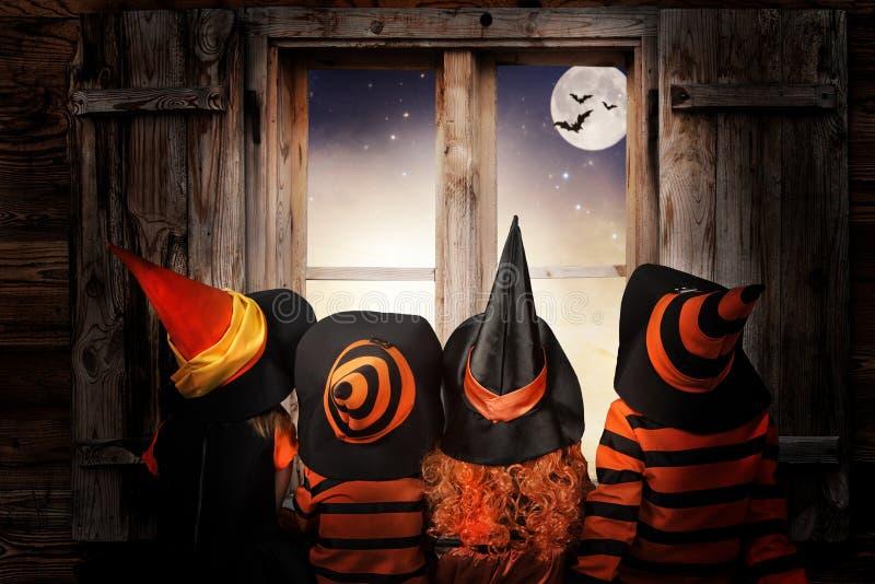 halloween Barn i dräkter av häxor och trollkarlen på natten sitter nära en fönsterandandblick på himlen och slagträna arkivfoton