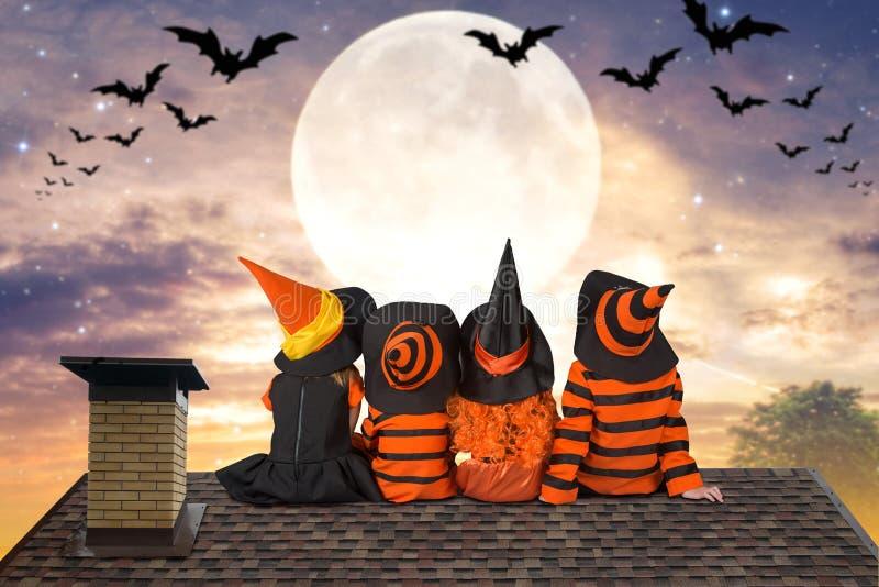 halloween Barn i dräkter av häxor och trollkarlen sitter att natten på taket och blicken på himlen och slagträna arkivfoto
