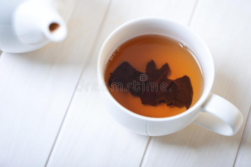 Halloween bat make from tea leaves into tea cup on white wooden table. Halloween celebration concept. Copy space stock photos