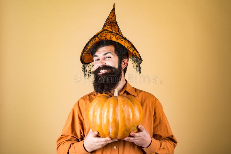Halloween beaded man hold pumpkin - portrait. Happy Halloween - handsome man isolated. Smiling happy man with pumpkin stock photos