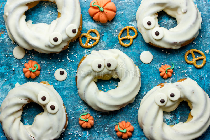 Halloween behandelt, kleiner Monsternachtisch mit dem Donut, der in wh eingetaucht wird stockfotos