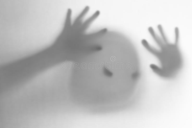 Halloween blurred background. A ghost resembling a pumpkin in color behind glass. Terrible and terrible nightmare. He knocks on the window royalty free stock photography