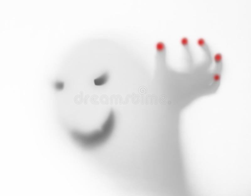 Halloween blurred background. A ghost resembling a pumpkin in color behind glass. Terrible and terrible nightmare. He knocks on the window royalty free stock image