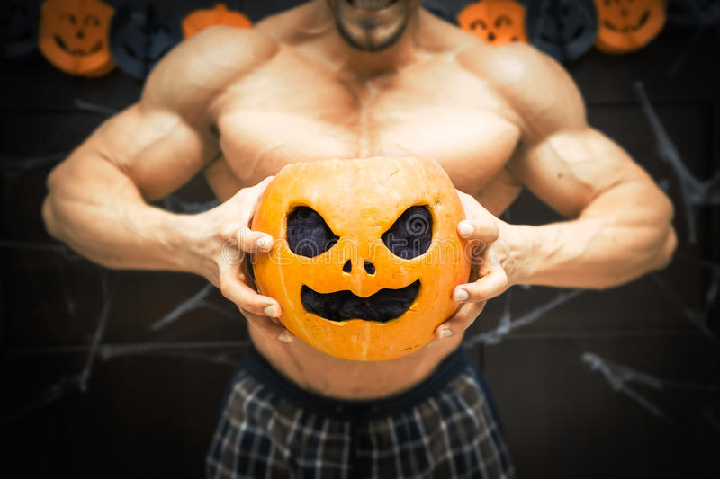 Halloween bodybuilder with pumpkin. Gym halloween theme gym halloween gourd bodybuilder with pumpkin in his hands, a strong man squeezes a pumpkin, sportsman's stock images