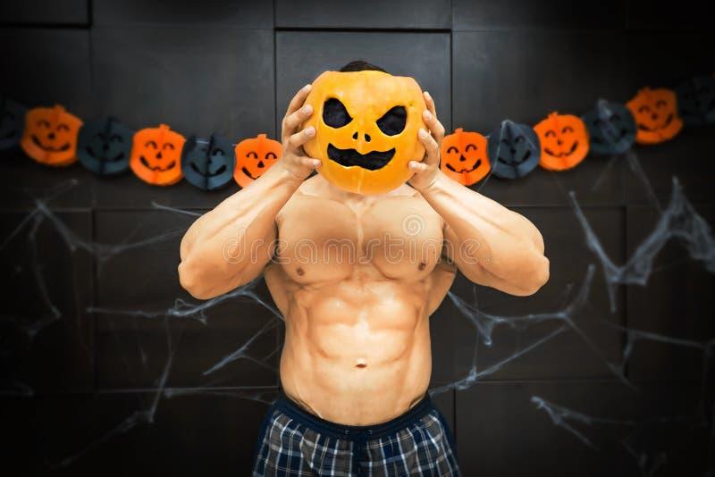 Halloween bodybuilder with pumpkin. Gym halloween theme gym halloween gourd bodybuilder with pumpkin near his head, a strong man squeezes a pumpkin, sportsman's stock photos