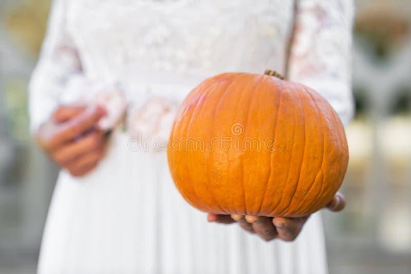 Halloween Bride holding pumpkin in her hands. Halloween Ghost Bride holding pumpkin in her hands stock image