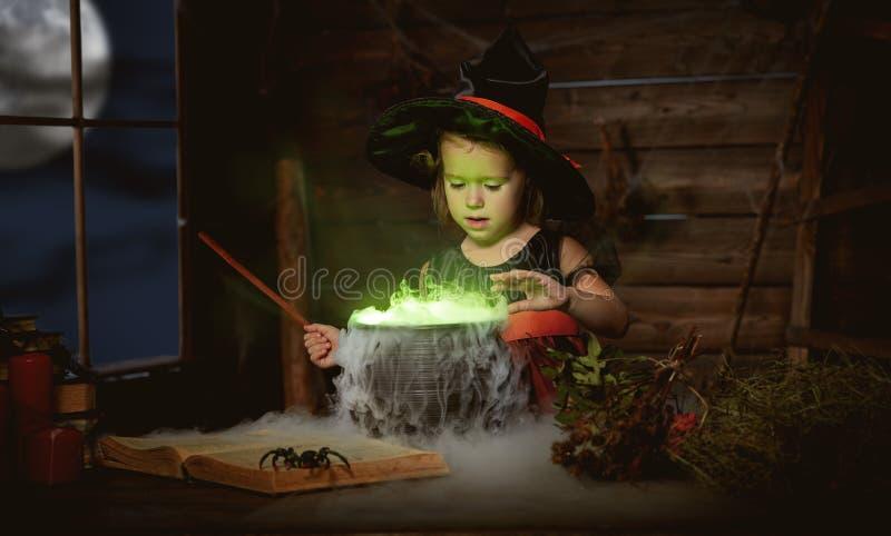 Halloween bruxa da menina da criança que prepara a poção no caldeirão foto de stock royalty free