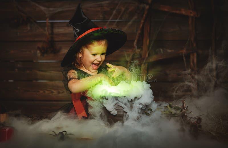 Halloween bruxa da menina da criança que prepara a poção no caldeirão fotografia de stock
