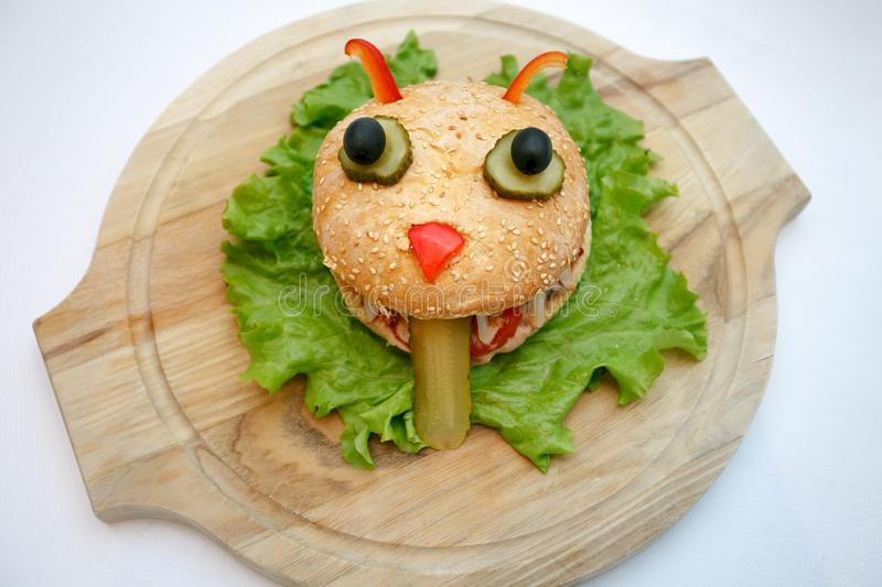 Halloween burger monsters ion wooden plate, food for kids party. stock photo