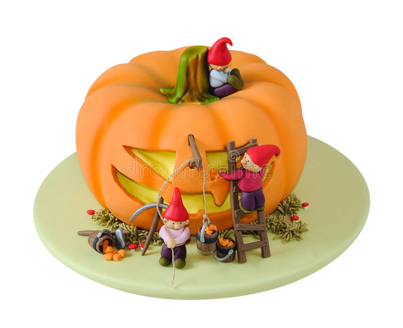 Halloween cake. Cute cartoon like cake with little gnomes cutting a halloween face out of a pumpkin. Cake is made with fondant sugar paste. Isolated on white