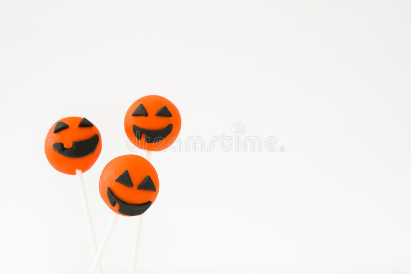 Halloween cake pops with pumpkin shape on white background royalty free stock photography