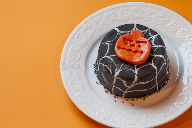 Halloween cake in a white plate. Surface orange background. royalty free stock images