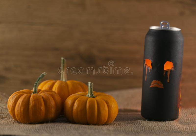 Halloween can and 3 pumpkins on textil and old wooden background. Concept Halloween background stock photos