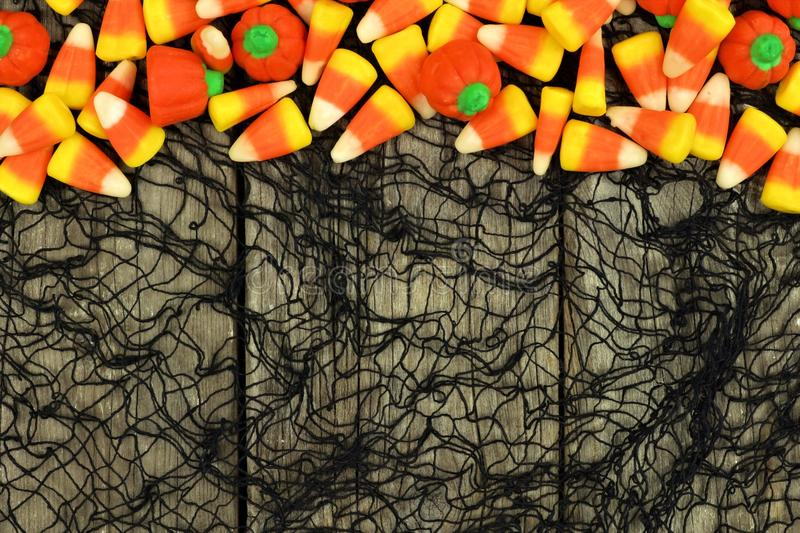 Halloween candy border against a wood and black cloth background. Halloween candy top border against a rustic wood and spooky black cloth background royalty free stock photos
