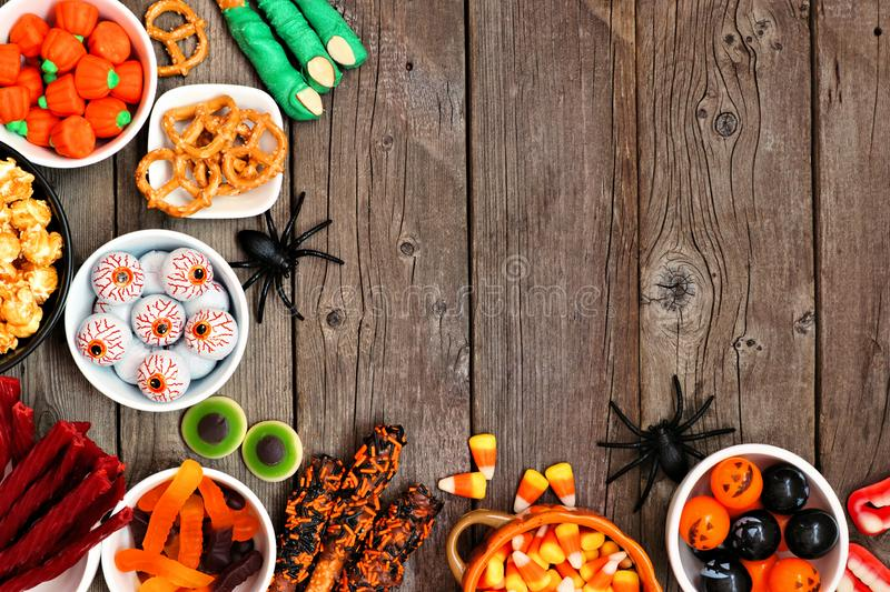 Halloween candy buffet table corner border over a rustic wood background with copy space. Halloween candy corner border over a rustic wood background with copy stock images
