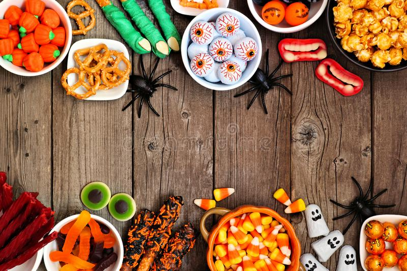 Halloween candy buffet table double border over a rustic wood background with copy space. Halloween candy double border over a rustic wood background with copy royalty free stock photo