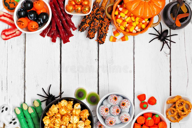 Halloween candy buffet table double border over a white wood background with copy space. Halloween candy double border over a white wood background with copy royalty free stock photos