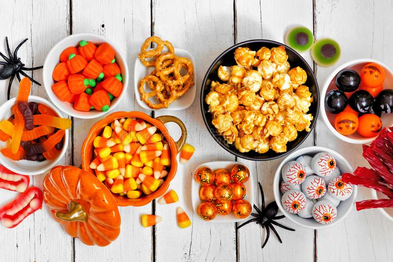 Halloween candy buffet table top view over a white wood background stock image