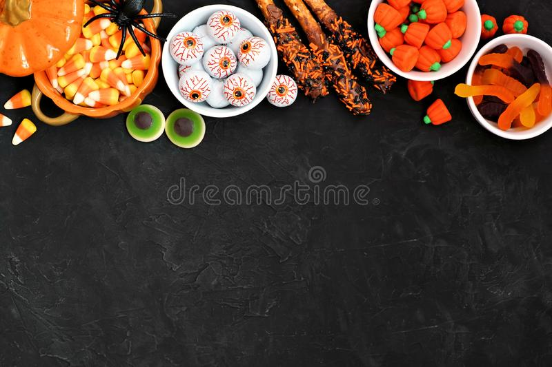Halloween candy buffet table top border over a black background with copy space. Halloween candy top border over a black stone background with copy space royalty free stock image