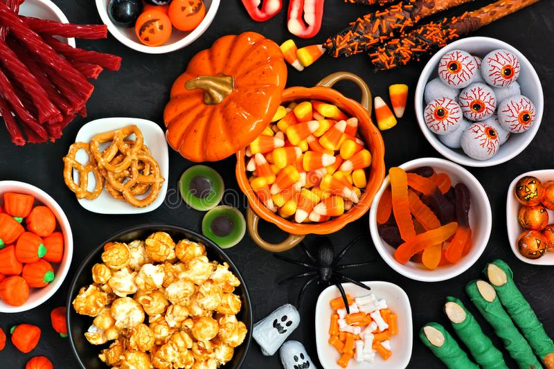 Halloween candy buffet table top view over a black background. Halloween candy buffet table scene over a black stone background. Assortment of sweet, spooky royalty free stock image