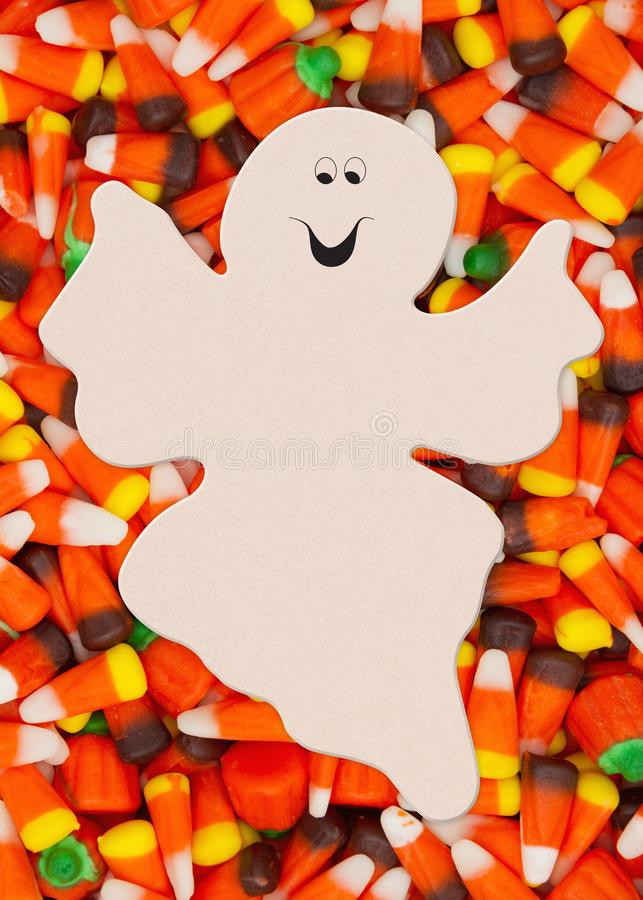 Halloween candy corn background with spooky ghost for your message. Halloween candy corn with candy pumpkins background with spooky ghost for your message stock images