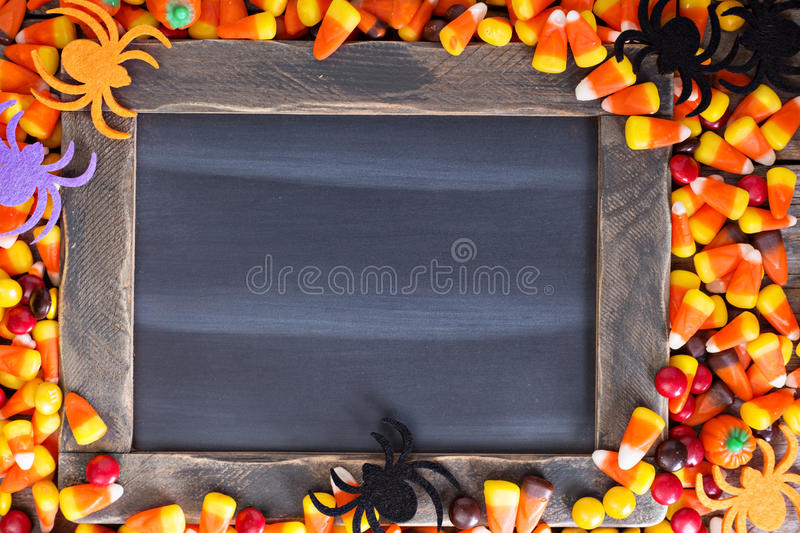Halloween candy frame around chalk board royalty free stock images