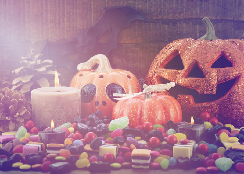 Halloween Candy with pumpkins on dark wood background. royalty free stock images