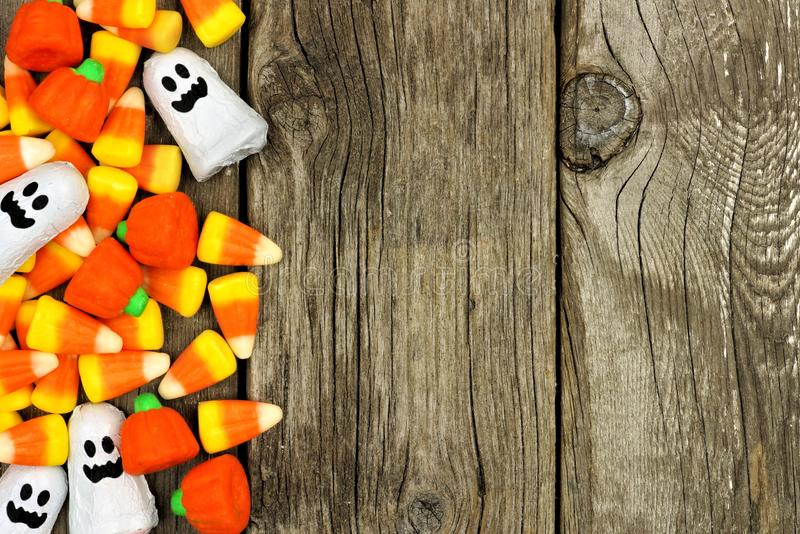 Halloween candy side border against rustic wood royalty free stock image