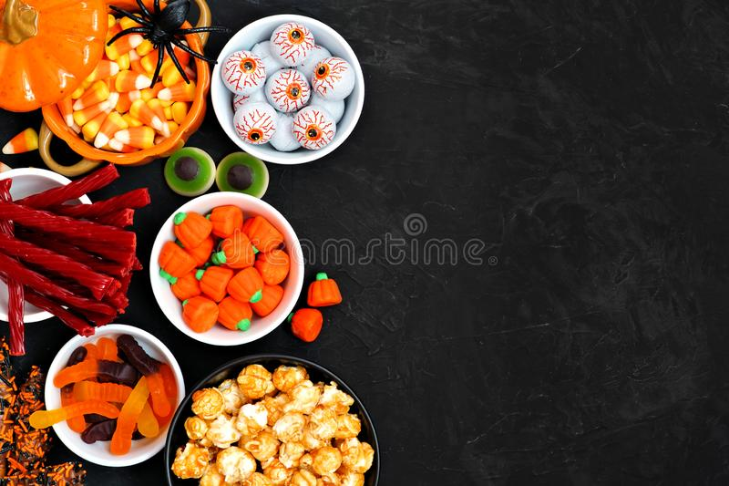 Halloween candy buffet table side border over a black background with copy space. Halloween candy side border over a black stone background with copy space stock image