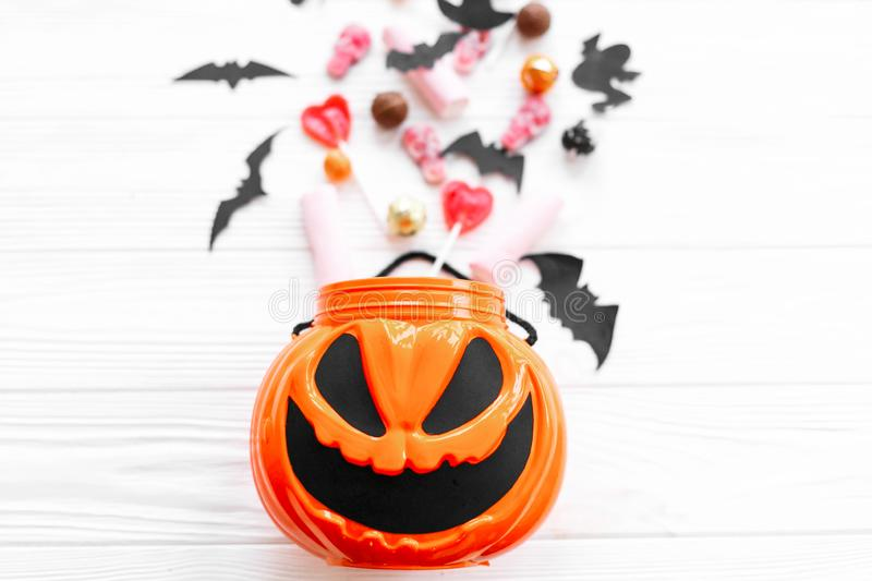 Halloween candy with skulls, black bats, ghost, spider decorations spilled from jack o lantern bucket on white wooden background,. Flat lay. Halloween sweets stock photos