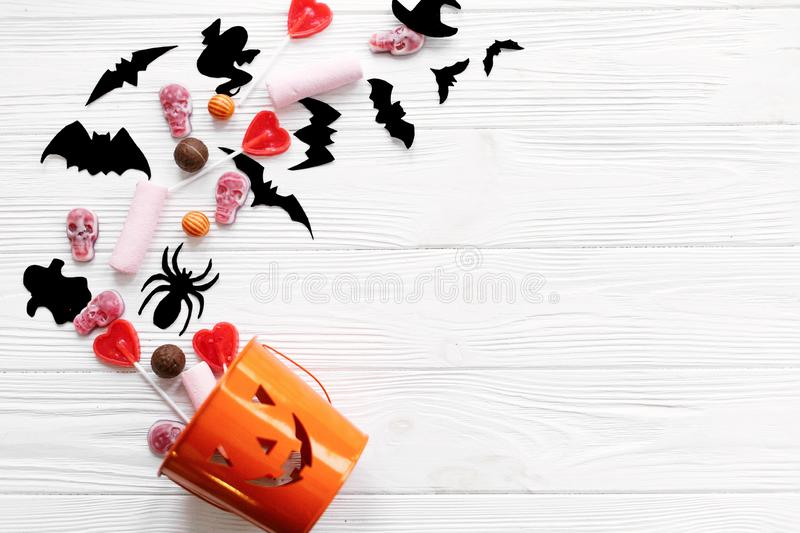 Halloween candy with skulls, black bats, ghost, spider decorations spilled from jack o lantern bucket on white wooden background,. Flat lay. Halloween sweets stock photography