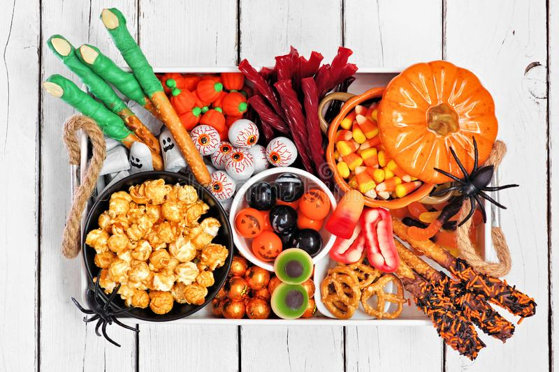 Halloween candy tray, top view over a white wood background. Halloween candy tray over a white wood background. Assortment of fun, spooky treats. Top view royalty free stock photos
