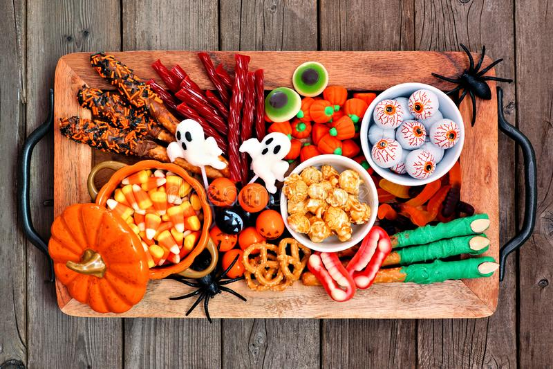 Halloween candy tray, top view over a rustic wood background. Halloween candy tray over a rustic wood background. Assortment of sweet spooky treats. Top view stock image