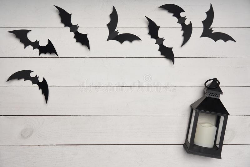 Halloween card. Black paper decoration bats and black lantern on white wooden planks. With blank copy space in center royalty free stock photo