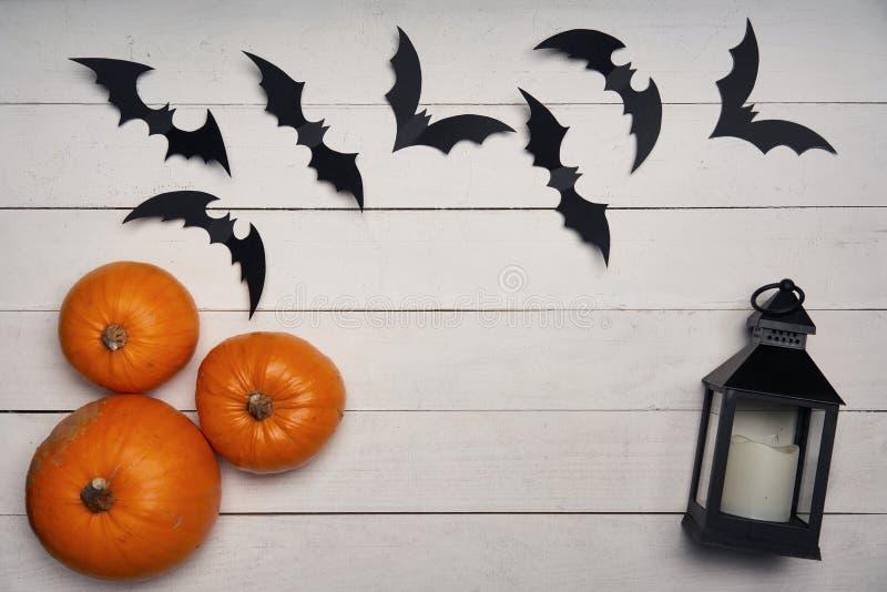 Halloween card with pumpkins, black bats and black lantern on white. Halloween card. Pumpkins, black paper decoration bats and black lantern on white wooden stock photos
