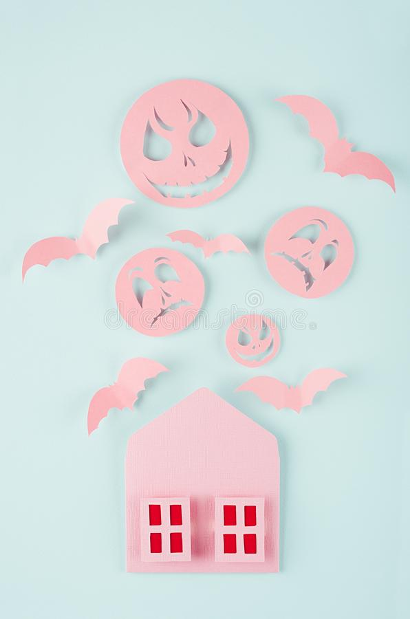 Halloween celebration card - pink spooky house with bloody window, swarm bats and monster face of cut paper on pastel green color. royalty free stock photography