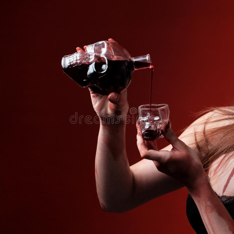 Bottle and glass in the form of a skull. Female hands pour wine or blood. Red background. Halloween celebration concept. Close-up stock photography